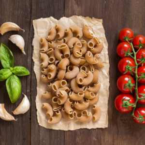 whole-wheat-pasta-with-garlic-tomatoes-basil-wooden-table 1